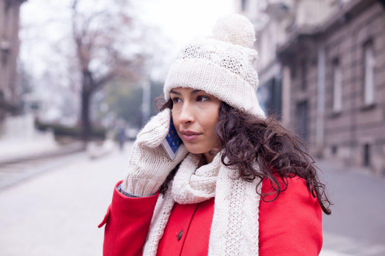 Young woman talking on smart phone while standing in city