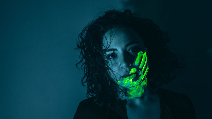 Woman with neon face paint against black background