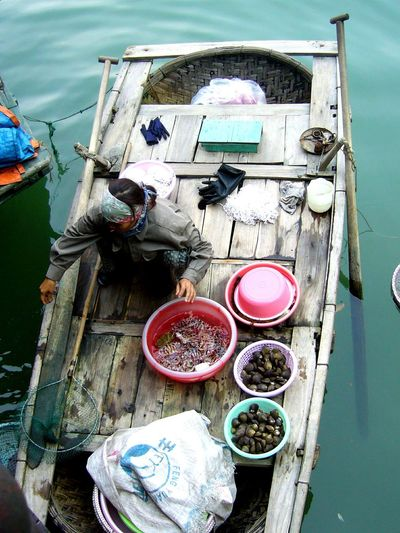 Female vendor with seafood in boat at floating market