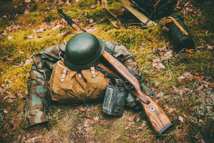 Military uniform and weapon on land in forest