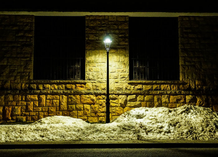 Illuminated street light against building during winter