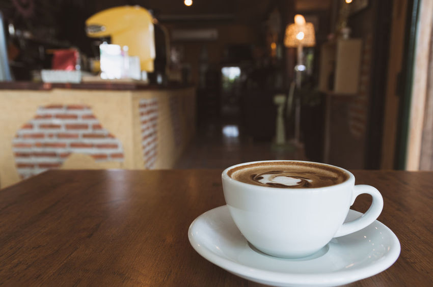 A coffee cup on wooden table in coffee shop and copy space. Drink Coffee Table Food And Drink Coffee Cup Refreshment Coffee - Drink Cup Mug Crockery Still Life Saucer Indoors  Focus On Foreground Freshness Hot Drink Frothy Drink No People Wood - Material Close-up Latte Non-alcoholic Beverage Coffee Shop
