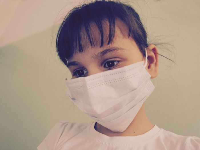 Close-up of girl wearing surgical mask