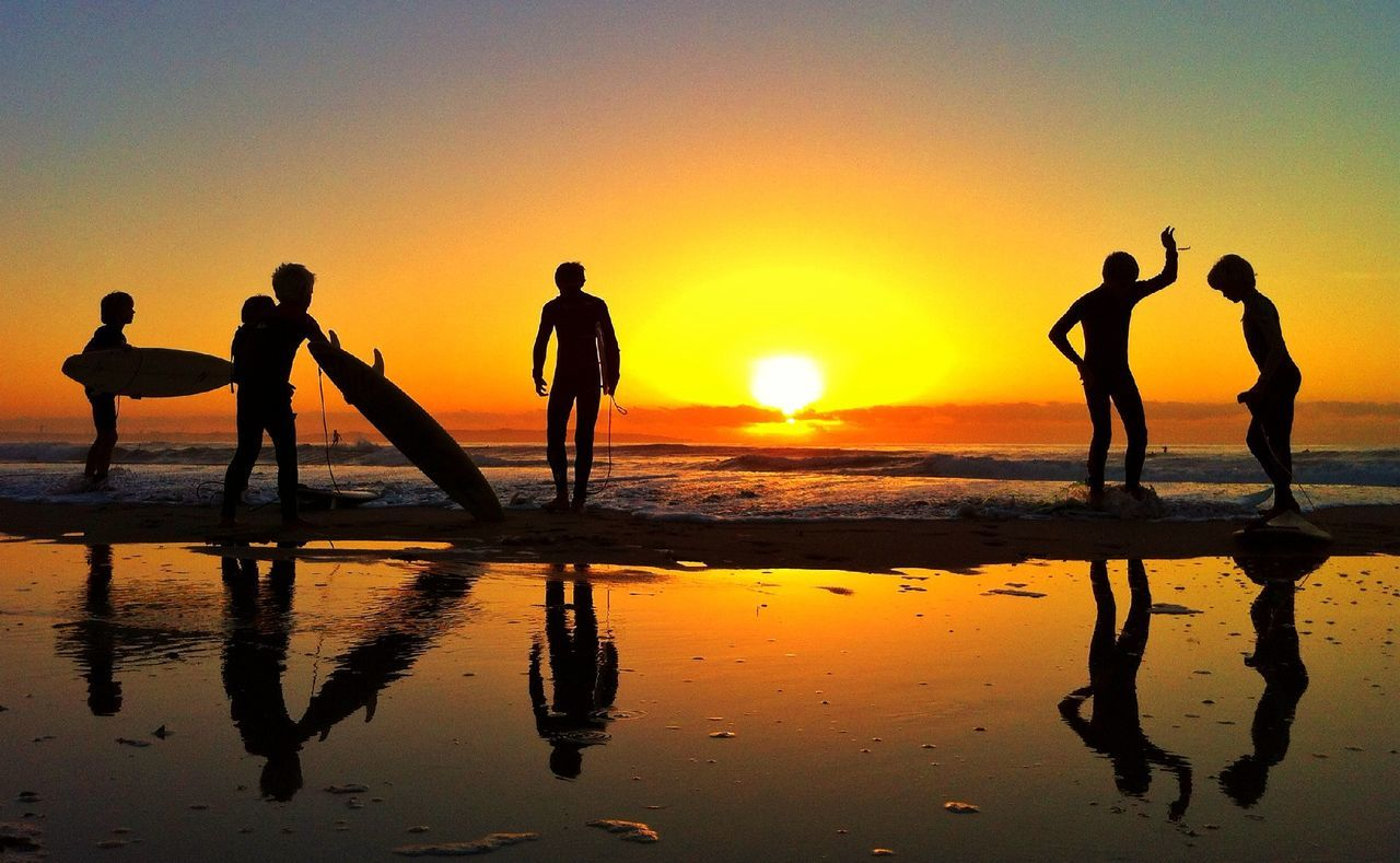 Silhouette people with surfboards walking on beach at sunset