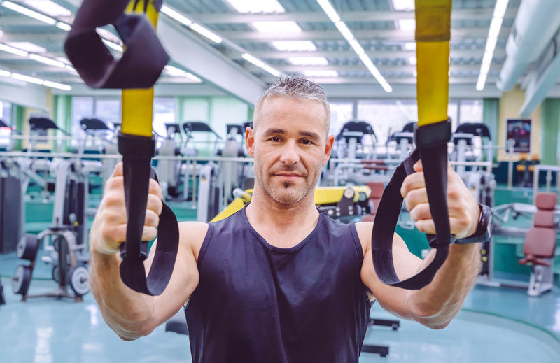 Portrait of man holding resistance band at gym