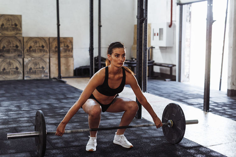 Young Female Athlete Exercising With Barbell In Gym