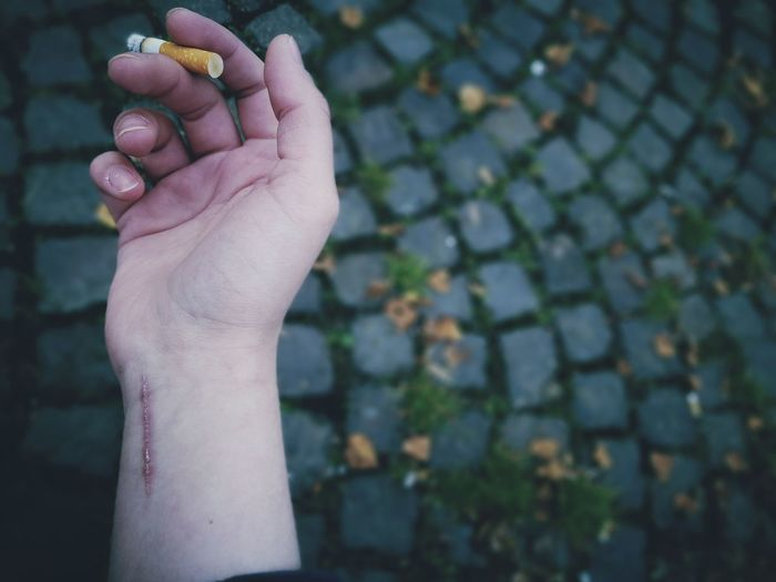 Close-Up Of A Hand With A Scar Holding A Cigarette