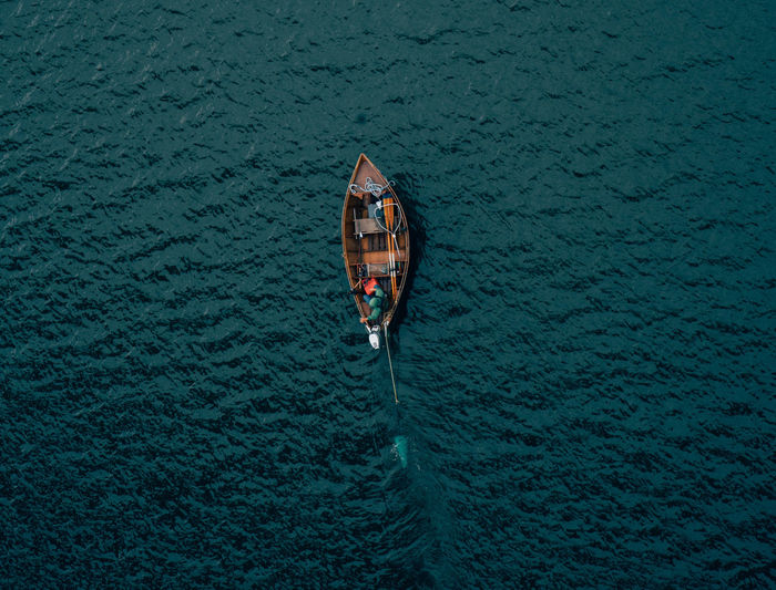 High angle view of person sitting in boat on sea