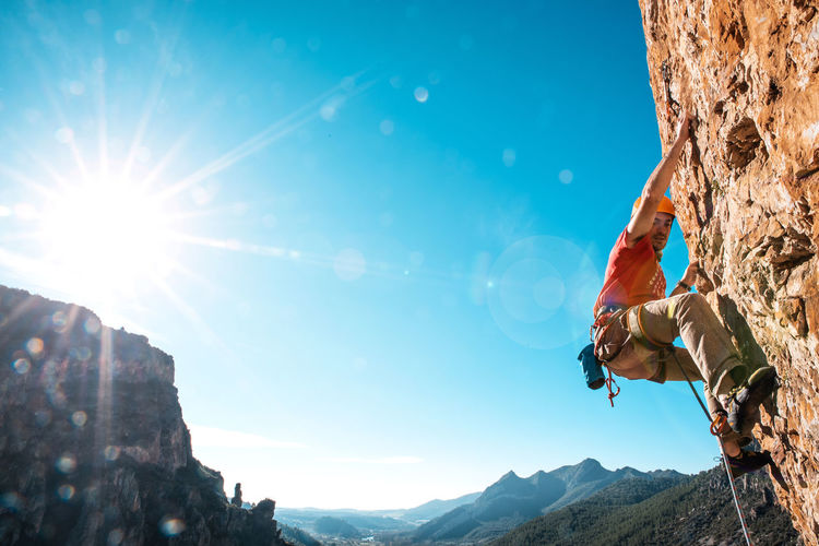 Climber Sunlight Mountain Sky Rock Nature Climbing Rock Climbing One Person Leisure Activity Adventure Extreme Sports Mountain Climbing Lens Flare Activity Outdoors Effort Sun Rock - Object Climber Brave Bold Sport Hot Sunny Day Red Rock
