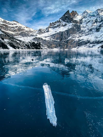 Scenic view of frozen sea by mountain