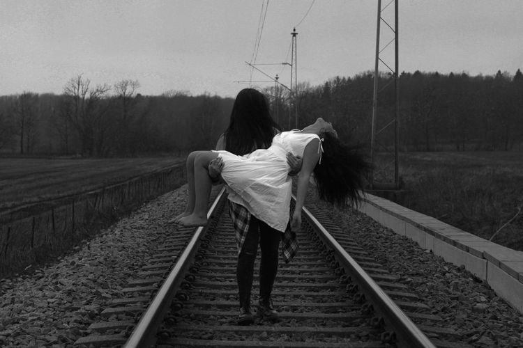 Woman carrying friend on railroad track