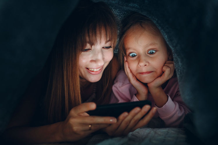 Mother and daughter watching video on smart phone