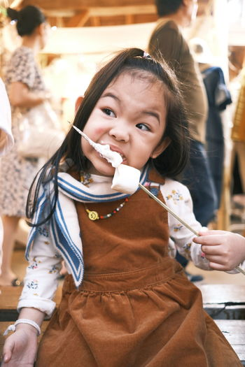 Cute childen eating marshmallow withe brown dress