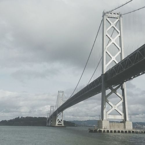 Low Angle View Of Bay Bridge Against Cloudy Sky