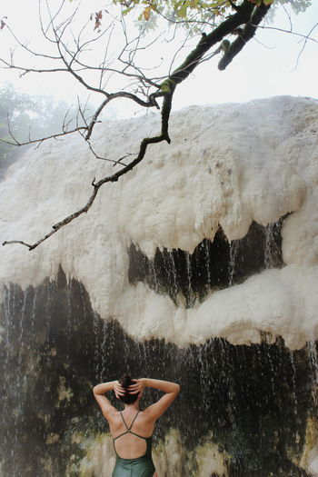 Woman standing by waterfall against trees