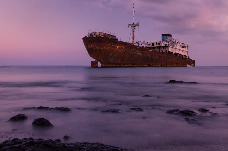 el Telamon ● Boat Stranded Stranded Boat Abandoned Abandoned & Derelict Sunrise Low Tide Arrecife Telamon Muelle Deck View Beached Beached Boat Violet Shades Of Sky Pink Sky Lanzarote Sea Beach Sunset Nautical Vessel Horizon Over Water Environment Ship Long Exposure No People Water Outdoors