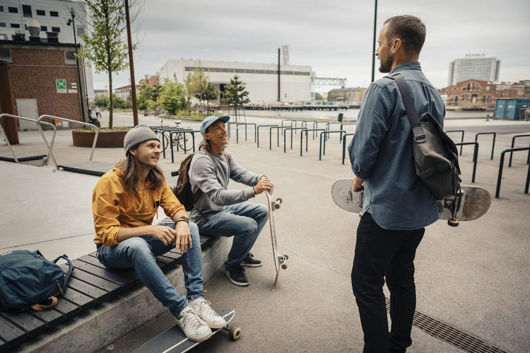 Full length of men sitting on sidewalk in city