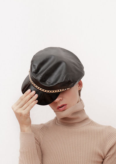 Woman holding hat in front of face against white background