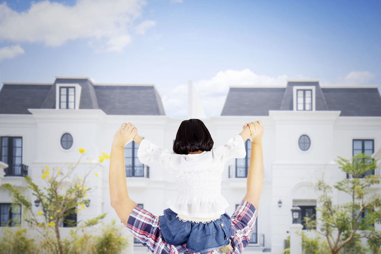 Rear view of woman sitting outside building against sky