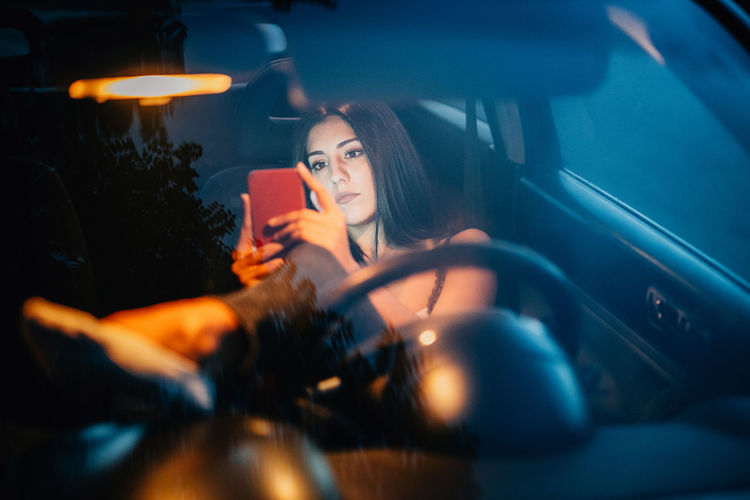 Young woman using smart phone while sitting in car