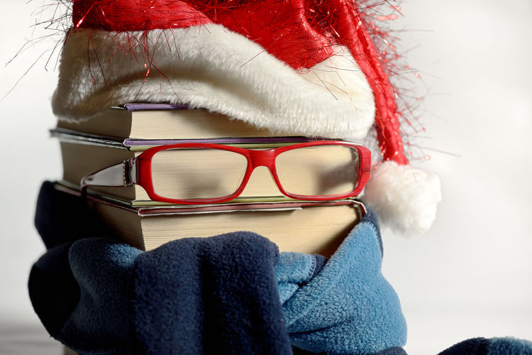 Close-up of stacked books with eyeglasses and santa hat against white background