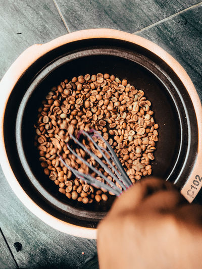 High angle view of hand holding coffee beans