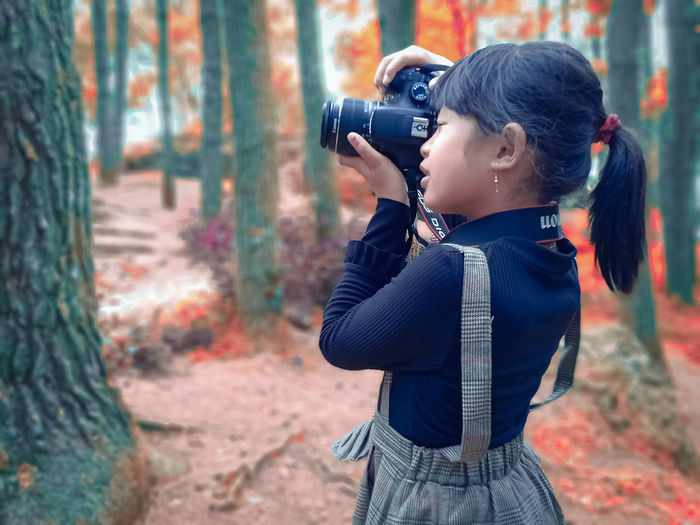 Side view of boy photographing in forest