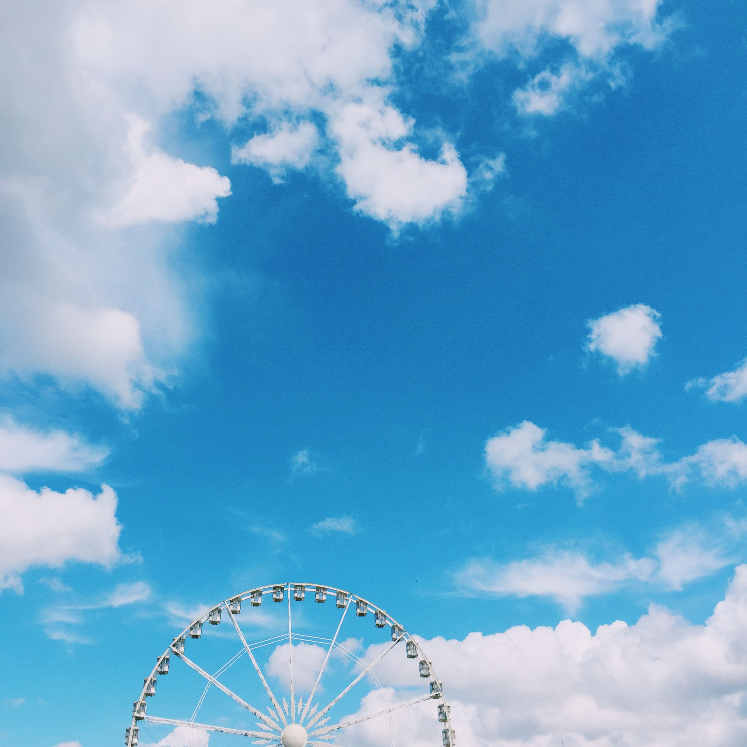 sky, low angle view, ferris wheel, amusement park, amusement park ride, cloud - sky, arts culture and entertainment, blue, cloud, cloudy, circle, day, fun, outdoors, pattern, no people, nature, metal, leisure activity, enjoyment