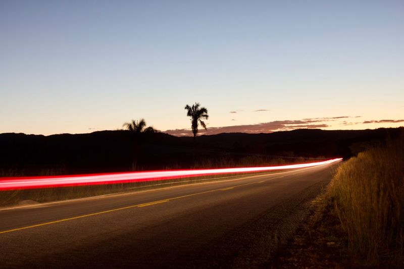 Light Trails On Road Against Clear Sky At Night