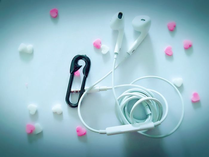 Directly above shot of in-ear headphones with heart shaped candies on white background