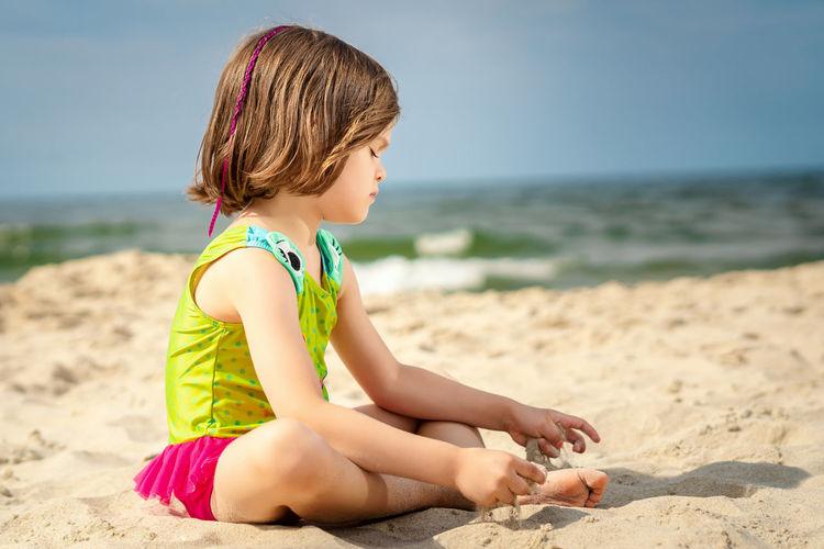 Girl relaxing on sand at beach against sky