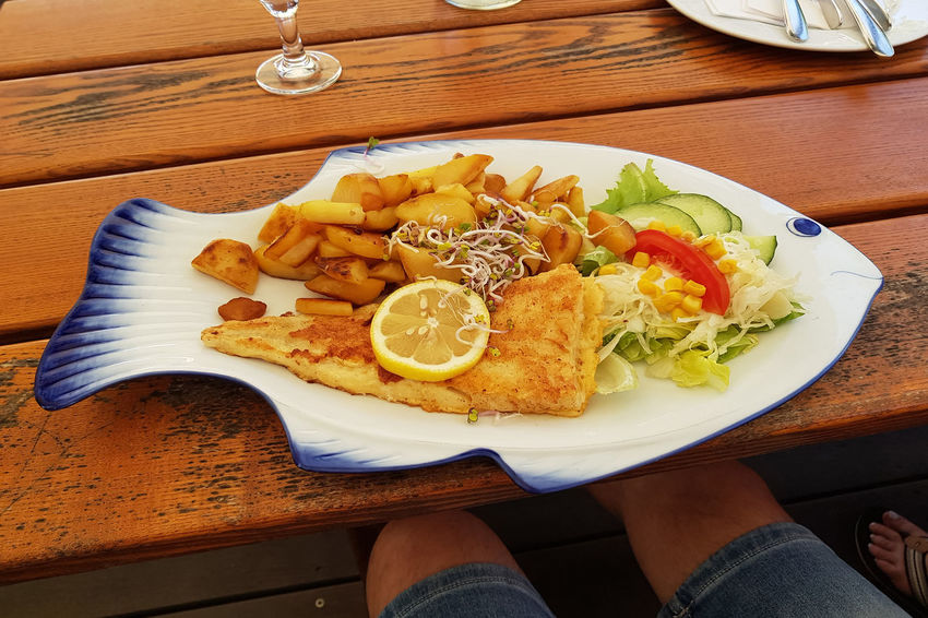 Fried fish with fried potatoes and lemon slices on fish-shaped plate Food Food And Drink Freshness Fruit Healthy Eating High Angle View Human Body Part Human Hand Indoors  Meal One Person Plate Ready-to-eat Real People Serving Size Table Unrecognizable Person Vegetable Wellbeing Wood - Material