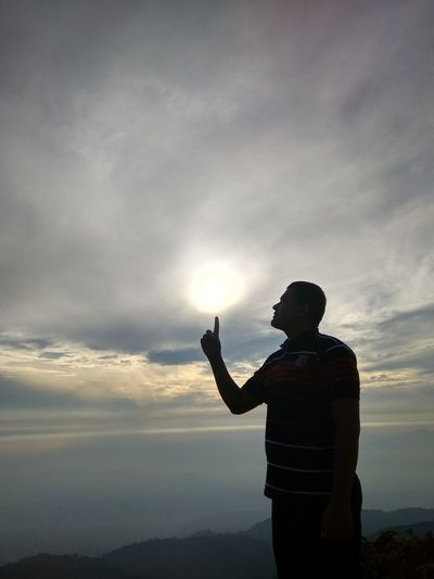 Optical illusion of silhouette man touching sun while standing against cloudy sky during sunset