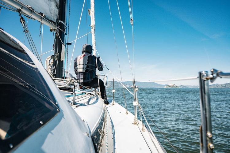 Heading forward Sea Mode Of Transportation Transportation Water Nature Real People Sky Sunlight Nautical Vessel Day Men Sailing Rope One Person Travel Rear View Sailboat Outdoors Boat Ocean View Passion On Water