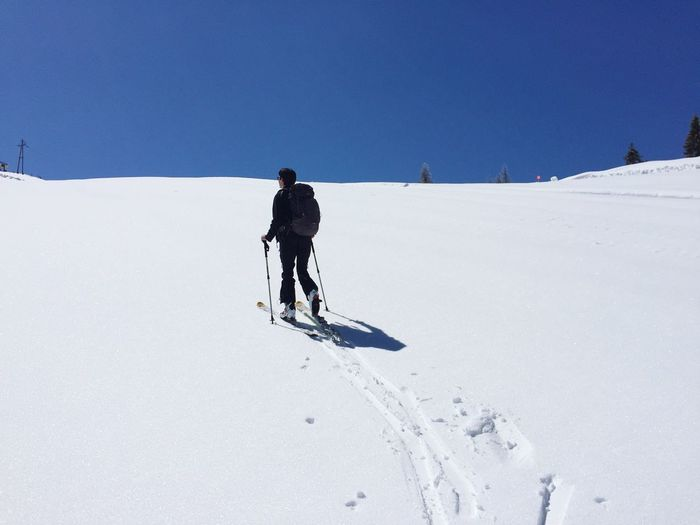 Rear view of person skiing on snow covered field against clear blue sky