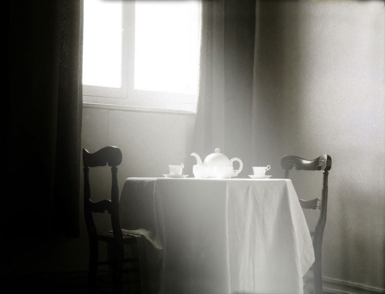 two chairs and a table with a white tablecloth a teapot and cups. Light coming in through window Calm Domestic Life Home Meditation Quiet Moments Romantic Sunday Tea Blackandwhite Photography Curtain Day Indoors  Interior Mystery No People Nostalgic  Peaceful Silence Togerherness Window