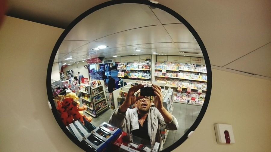 Reflection of woman photographing in mirror