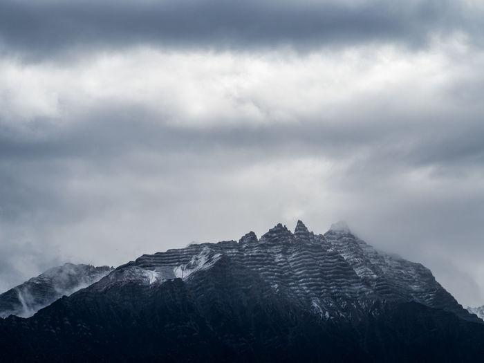 Unique snowy helmet like mountain cap under dense clouds, bomi, tibet, china