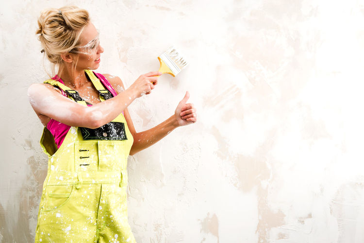 Female construction worker wearing coveralls while painting wall
