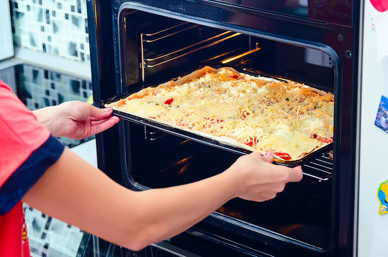 Close-Up Of Person Putting Pizza Into Oven