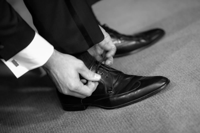Low Section Of Businessman Tying Shoelace On Floor