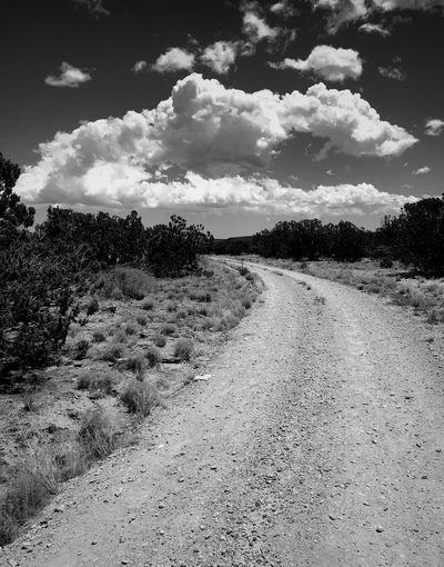 """Around The Curve And Into The Clouds"" A lonely country road in Central New Mexico leads to the clouds. New Mexico Photography New Mexico Skies New Mexico Clouds Dirt Road Country Road Roads Black And White Photography Black & White Black And White Sky Cloud - Sky Nature Day Landscape Tranquility"