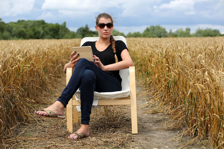 Portrait of beautiful young woman with digital tablet sitting on chair amidst farm