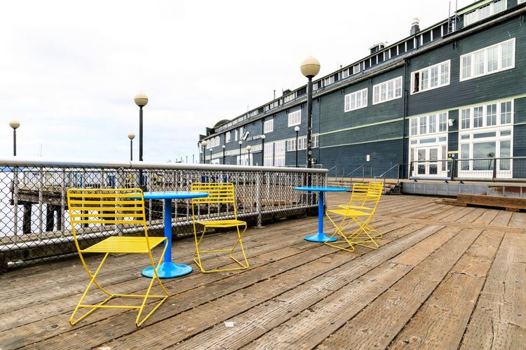 Seattle Dock Pier Table Chairs Architecture Built Structure Building Exterior Day Street Building No People Outdoors Railing Multi Colored Footpath City Absence Empty
