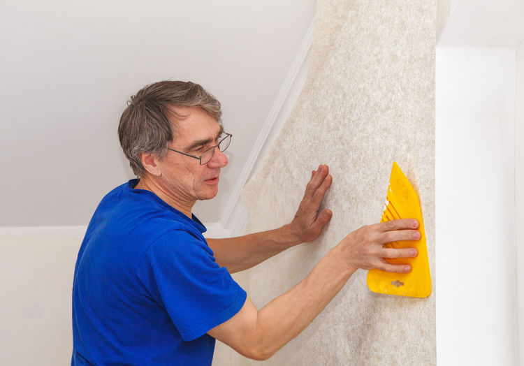 Mature painter using scrapper on wall