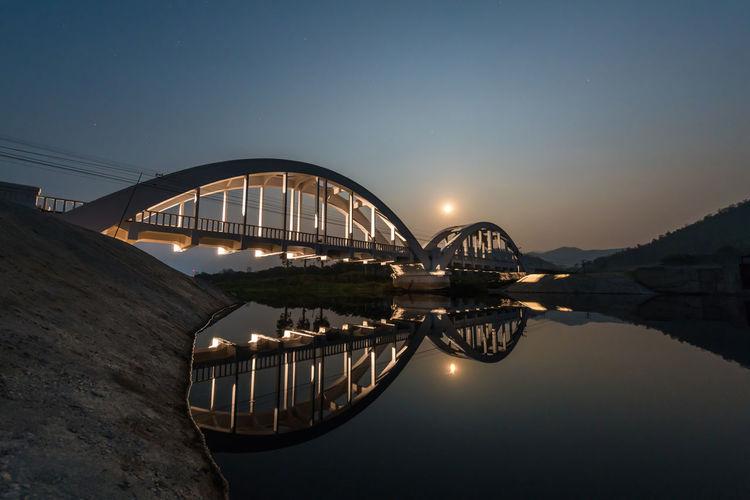 Bridge over river against sky at night
