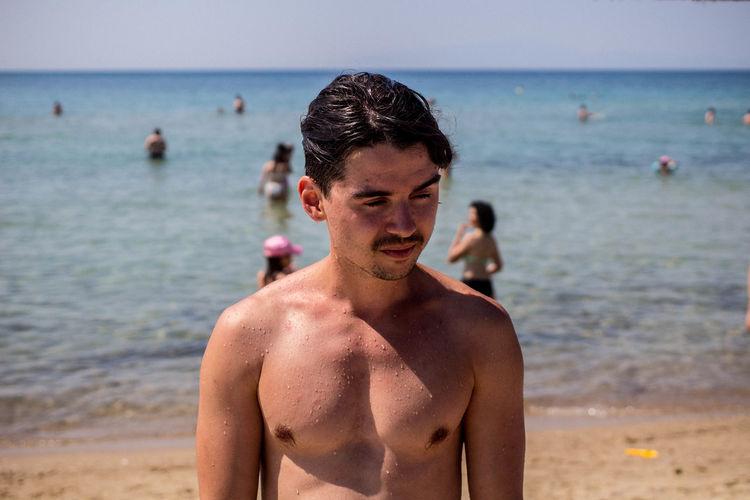Close-Up Of Shirtless Man Standing At Beach
