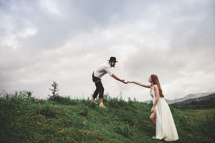 Beautiful young couple in love walking in nature. He helps his bride to climb the hill. She is dressed in a white wedding dress, and the groom wears a black hat and is dressed in a shirt and pants with suspenders. He has a beard on his face. Photo of two attractive people. The grass grows in the meadow. Above the head is the sky with clouds. Couple Family Fashion Freedom Happiness Happy Happy People Lifestyle Love Nature Peole And Places Relationship Wedding Couple - Relationship Couple In Love Happy Time Leasure Activity Lifestyles Peolpe Together Together Forever Togetherness Two People Wedding Day Wedding Dress