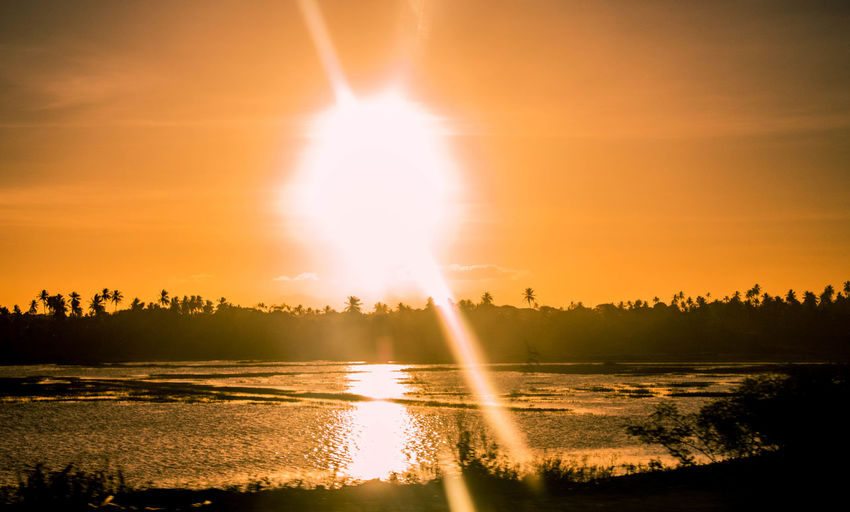 sunset Beauty In Nature Day Lake Lens Flare Nature No People Outdoors Reflection Scenics Silhouette Sky Sun Sunbeam Sunlight Sunset Travel Destinations Tree Water