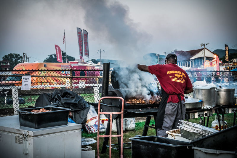 Real People Men Standing Smoke - Physical Structure Day Occupation One Person Sky Food Outdoors Working Food And Drink Container Nature Three Quarter Length Preparation  Barbecue Rear View Casual Clothing Preparing Food